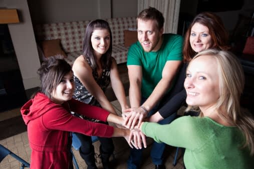 5 people with their hands together at 12 step recovery