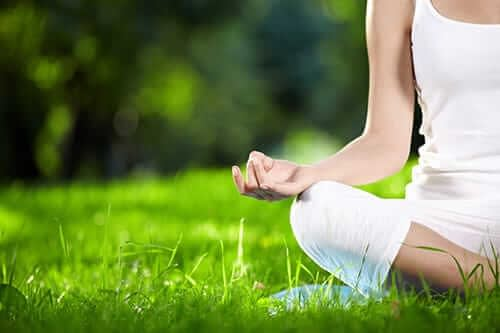 A woman meditates in the grass outside as a part of her holistic healing program