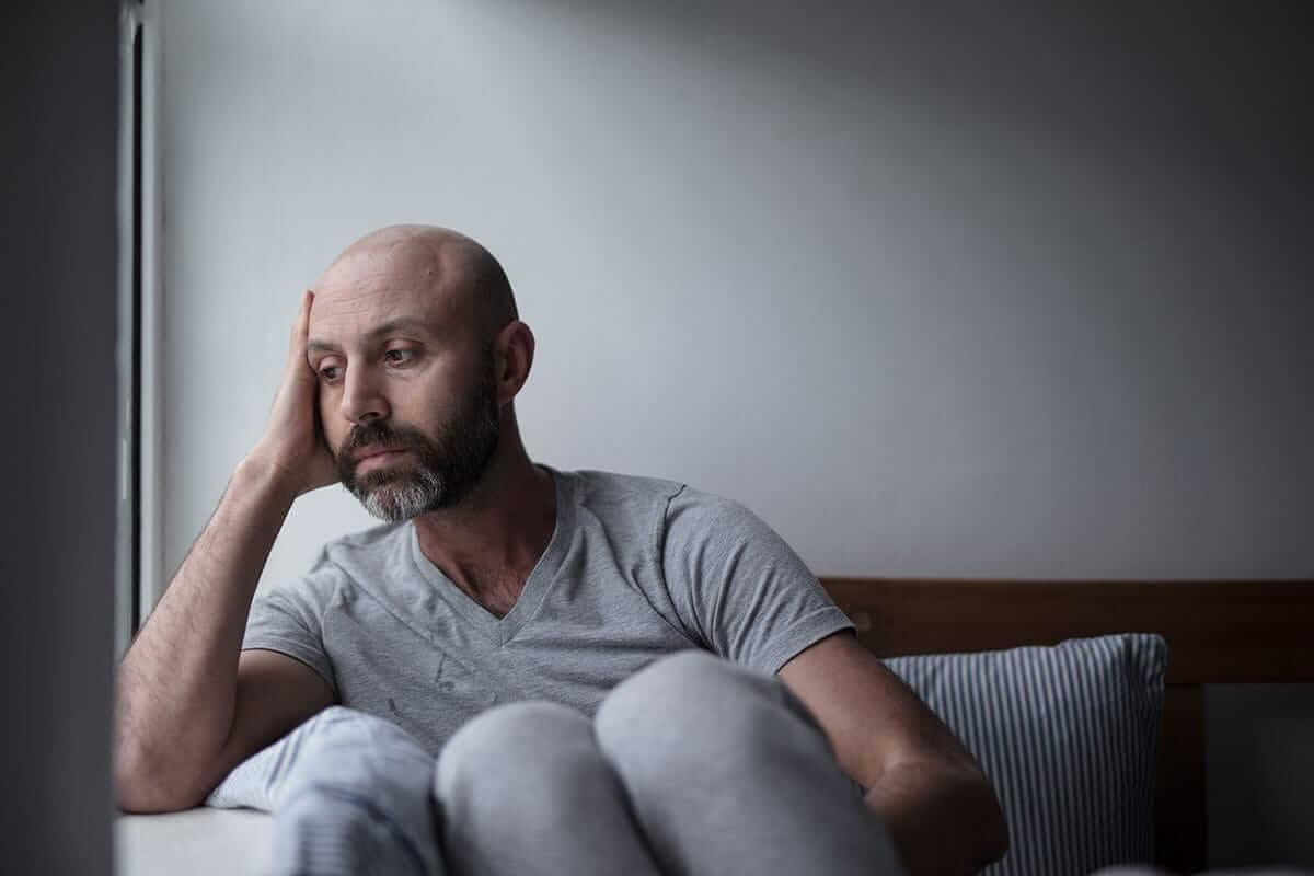 stressed man sitting on bed wondering how long does suboxone stay in your system