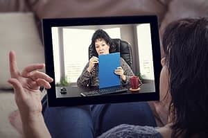 a woman uses an ipad to enroll in a telehealth intensive outpatient treatment program