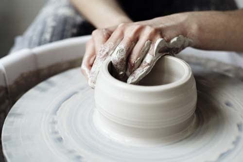 person making clay bowl on pottery wheel