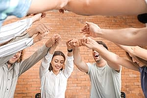 people in a circle raising and holding hands at an alcohol rehab center near West Linn