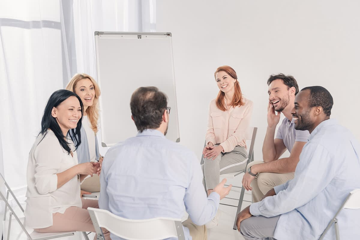 group of people smiling in a support group at a drug rehab in castle rock wa