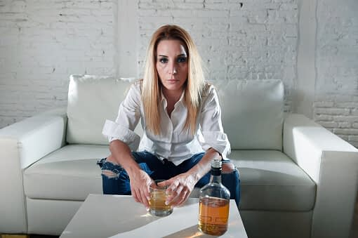 alcoholic woman sitting at home wonders is alcoholism a disease