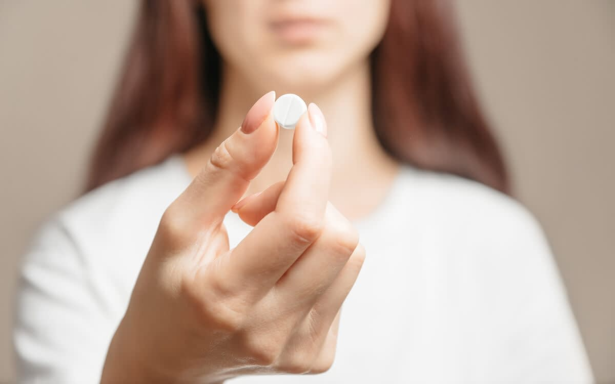 a woman holds a white pill and wonders about the opiate definition