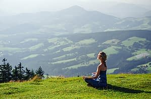 Holistic rehab may include yoga in a meadow, like this young woman.