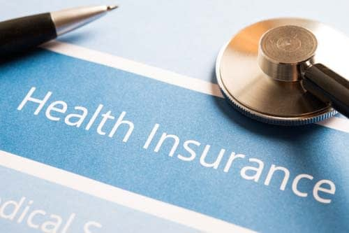health insurance document with stethoscope and pen