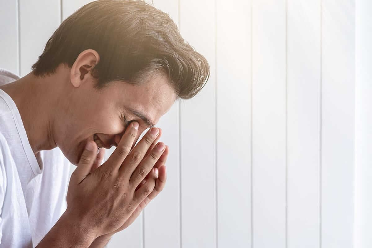 man holds face trying to maintain his emotional sobriety