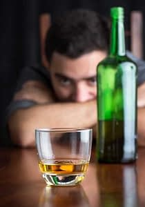 A man rests his head on his arms and stares at a glass of alcohol while he thinks about quitting drinking