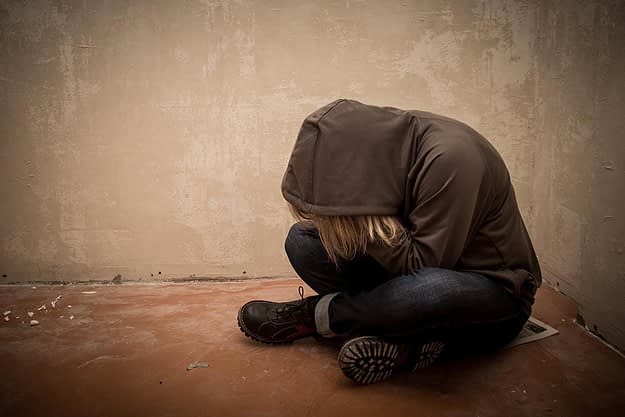 girl sits down with her head down thinking about drug addiction treatment
