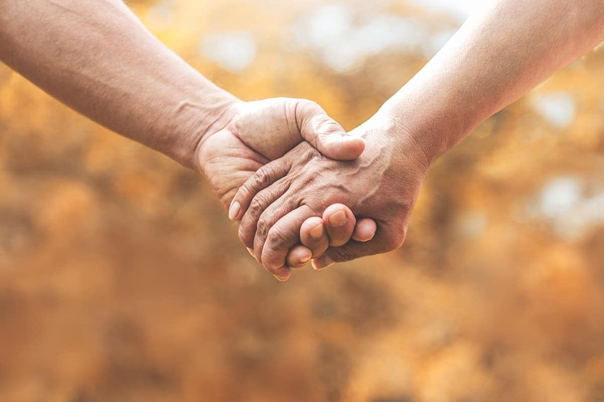 hand holding with a sponsor in recovery