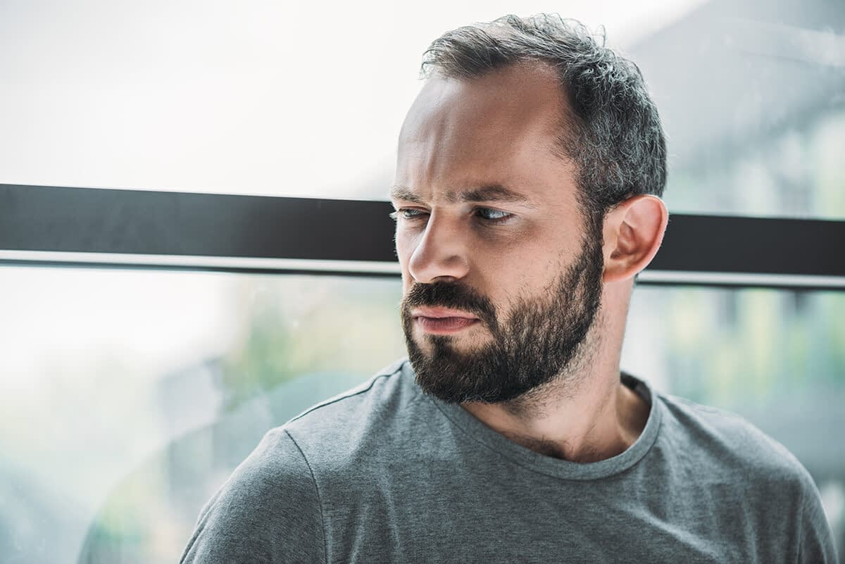 man sitting next to window and thinking on national drug takeback day