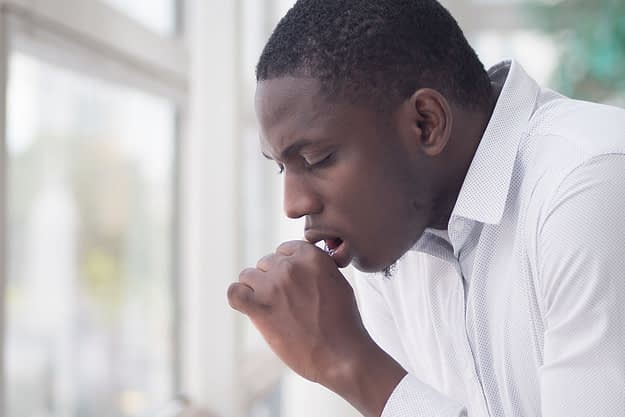 a man coughs as he considers addiction and your physical health