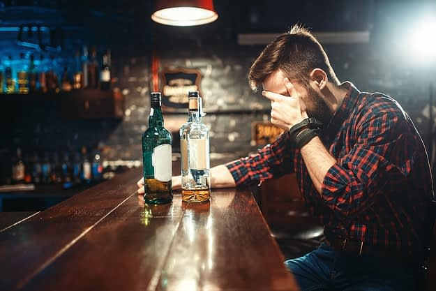 man in a bar struggling with beating alcoholism