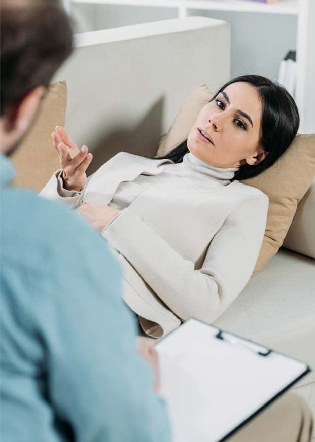 woman lying on couch in therapy session