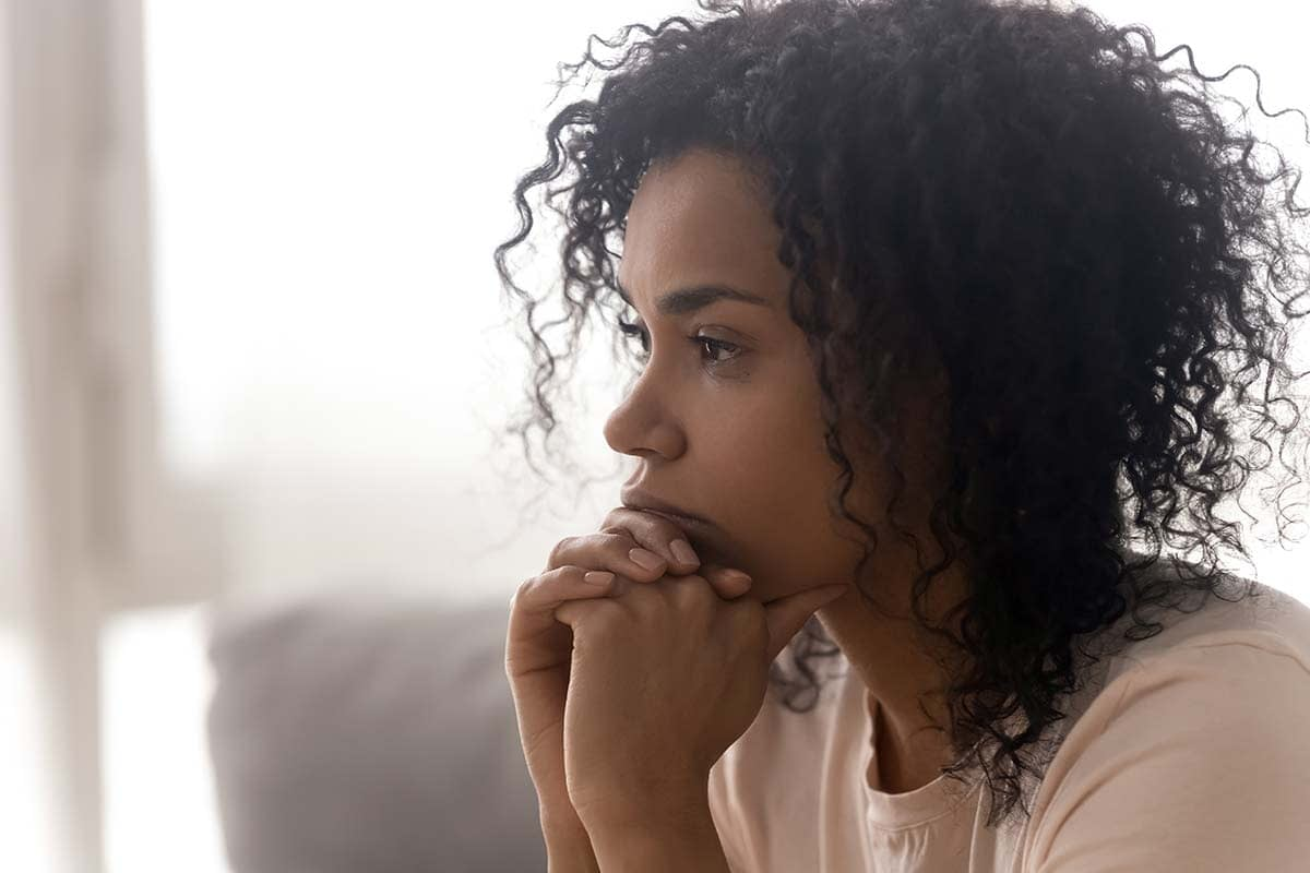 woman sitting on couch thinking about what is chemical dependency before taking medication