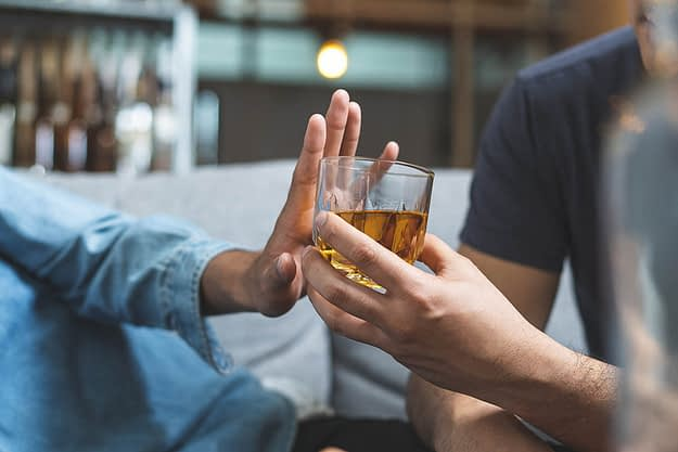 man handing a friend a drink as they push it away questioning how long does it take to detox from alcohol