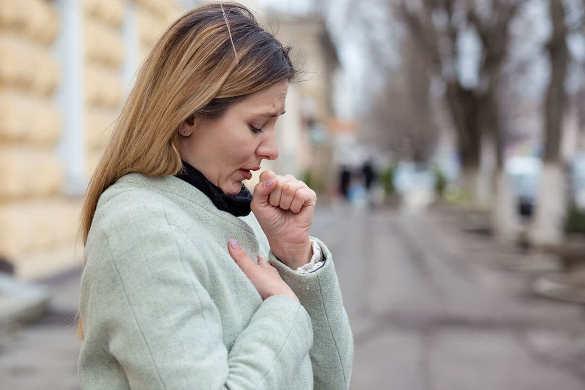 a woman coughs because she has a compromised immune system