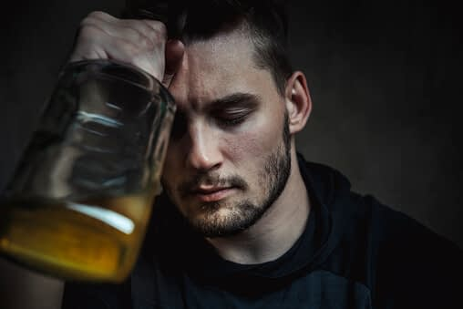 man holding a bottle is exhibiting the stages of alcoholism