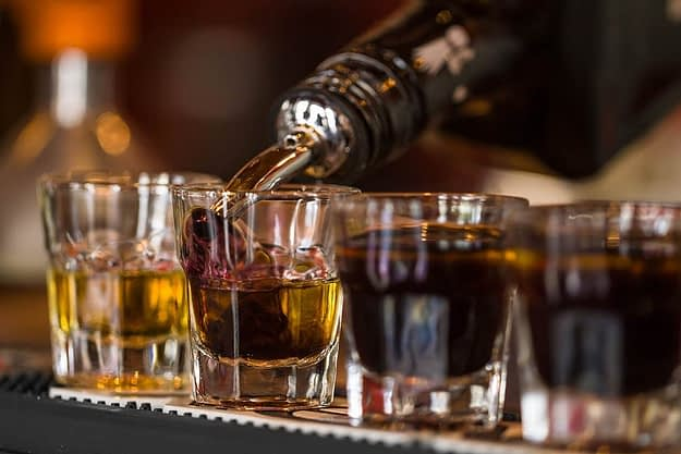 a bartender pouring drinks while asking is alcohol a stimulant