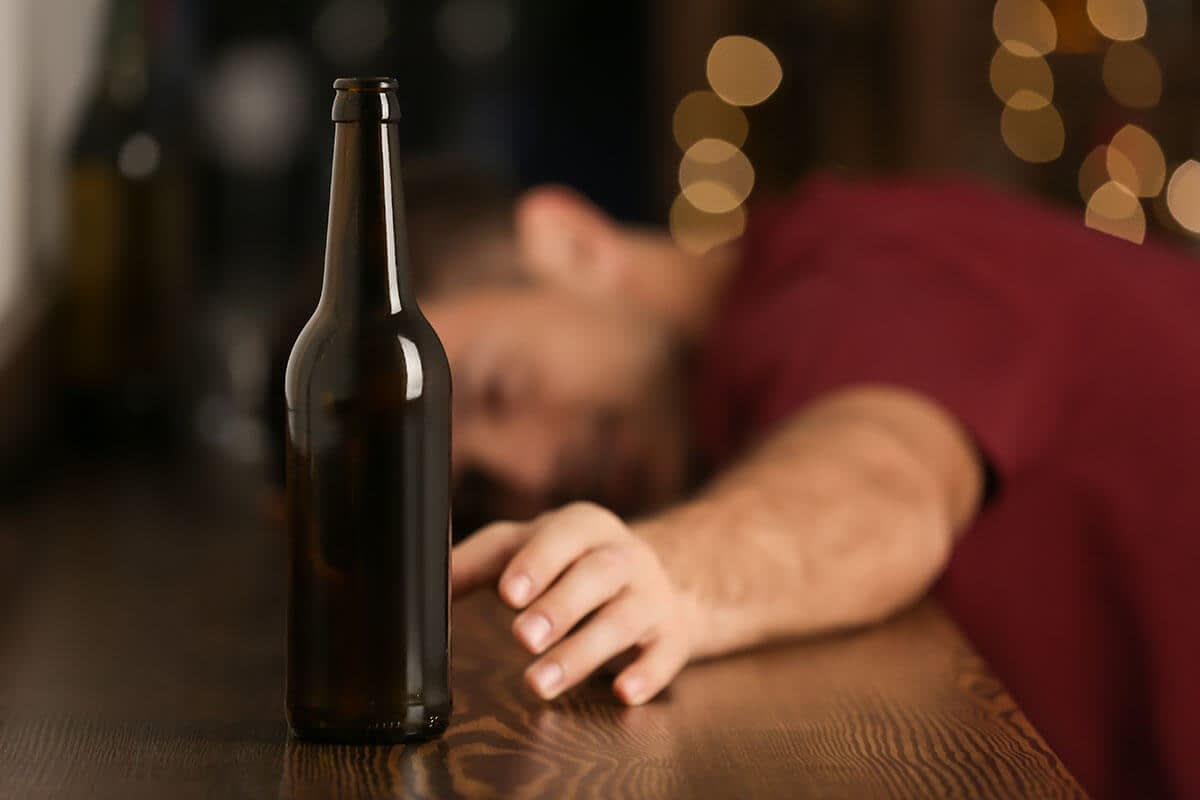 man suffering from the dangers of binge drinking