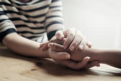 two people hold hands at addiction counseling