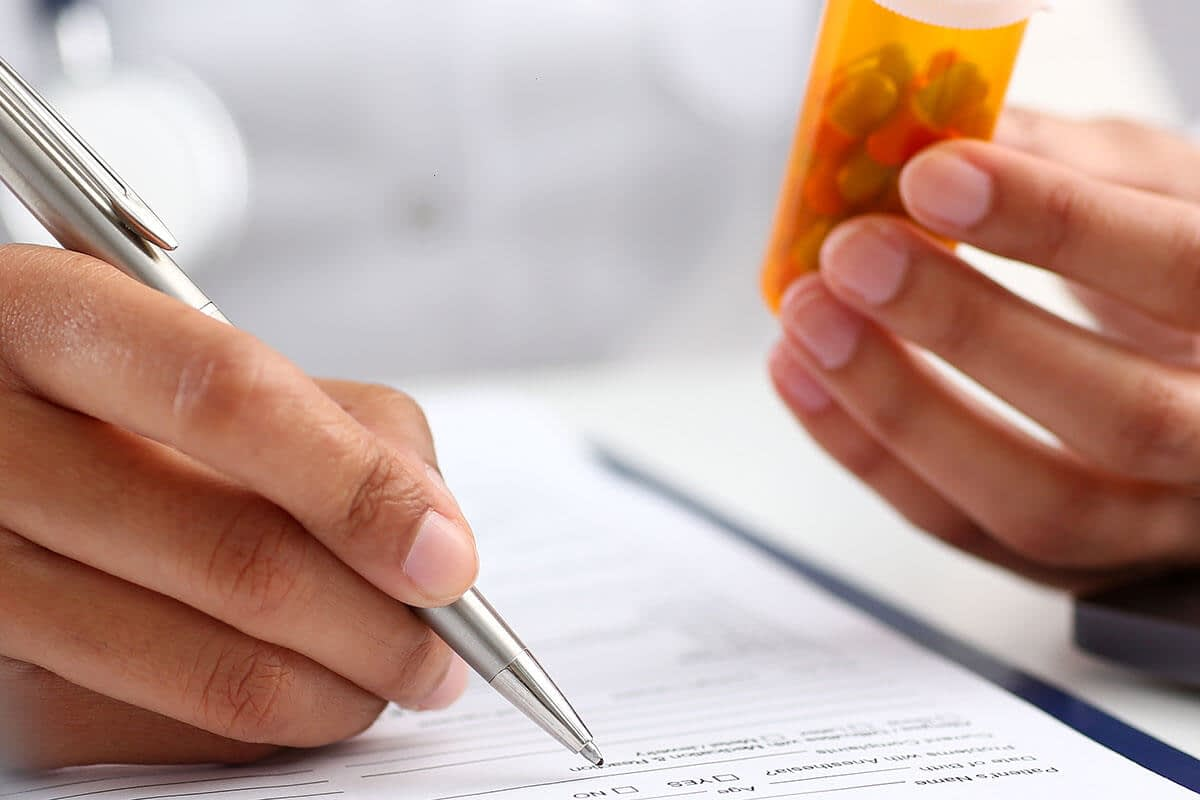 a doctor writes a prescription and thinks about the drug facts you should know