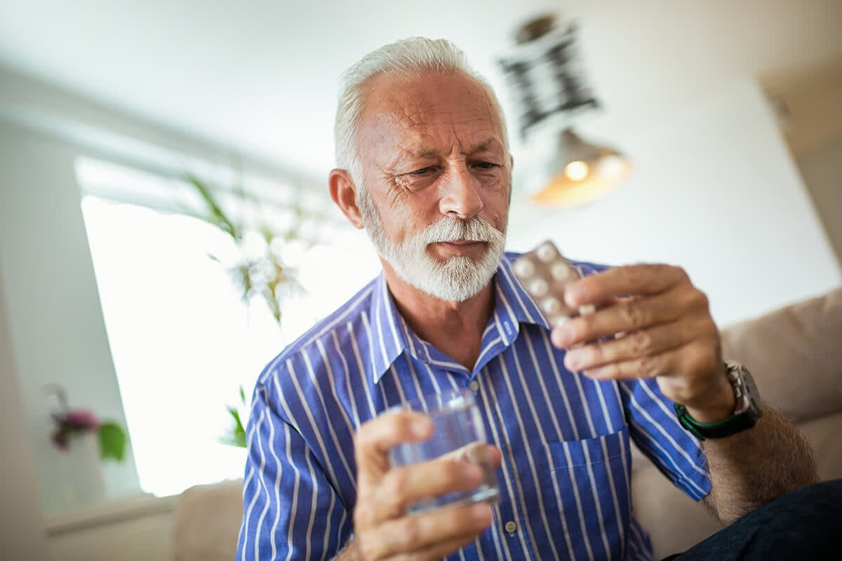 a man stares at pills and wonders about the difference between dependence vs addiction