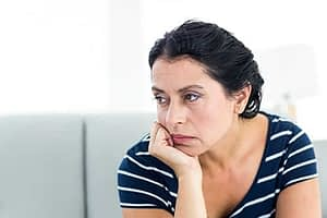 A woman rests her chin on her hand as she wonders if she has an addictive personality