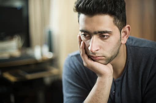 man sitting downs displays heroin addiction symptoms