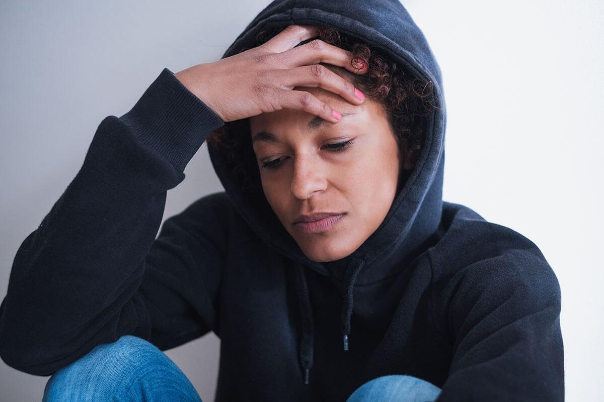 woman sitting down upset at a drug rehab