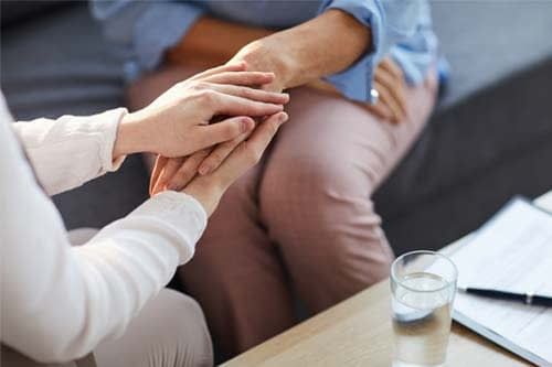 therapist holding patient's hand