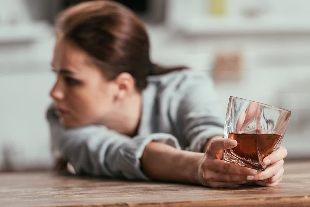a woman pushes away a glass of alcohol as she thinks about mental health and substance abuse
